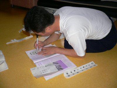 紙を切って、戒名を書いています。毎年、使い終わると燃やすそうです。