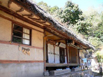 韓国の昔からの家。竹葺きの屋根に黄土の壁。家訓が外に飾ってあります。